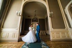 有佩带在曲拱的花束和英俊的新郎的美丽的新娘蓝色衣服跳舞在黄色围住背景 免版税库存照片