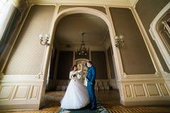 有佩带在曲拱的花束和英俊的新郎的美丽的新娘蓝色衣服跳舞在黄色围住背景 库存照片