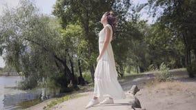有佩带在江边的长的深色的头发的画象可爱的少女一个长的白色夏天时尚礼服身分 影视素材