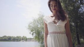 有佩带在江边的长的深色的头发的画象逗人喜爱的少女一个长的白色夏天时尚礼服身分 影视素材
