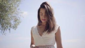 有佩带在的长的深色的头发的画象美丽的少女一个长的白色夏天时尚礼服身分 股票视频