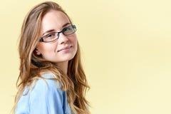 有佩带放大镜,黄色背景的微笑的女孩的姜头发和雀斑的美丽的少年女孩 免版税图库摄影
