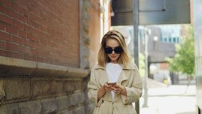 有佩带时髦外套和太阳镜的金发的走可爱的少妇在现代城市使用巧妙的电话 股票视频