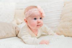 有佩带白色衣裳和桃红色带与花的胖的面颊的惊奇逗人喜爱的矮小的婴孩说谎在床上与被编织的枕头 免版税库存图片