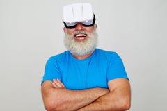 有佩带虚拟现实的横渡的胳膊的微笑的年迈的人朝向 免版税库存照片
