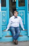 有佩带蝶形领结和摆在城市街道的短发的年轻英俊的人 库存图片