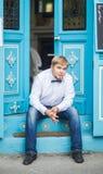 有佩带蝶形领结和摆在城市街道的短发的年轻英俊的人 库存照片