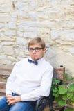 有佩带蝶形领结和摆在城市街道的短发的年轻英俊的人 免版税库存图片