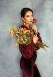 有佩带酒的clothers和金首饰的华美的干燥玫瑰花束的年轻可爱的时髦的深色的妇女  免版税图库摄影