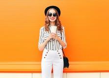 有佩带黑帽会议白色的咖啡杯的画象时尚微笑的妇女气喘在五颜六色的桔子的提包传动器 免版税图库摄影