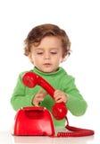 有使用与一个红色电话的一岁的婴孩 免版税库存照片