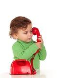 有使用与一个红色电话的一岁的婴孩 库存图片