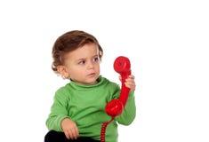 有使用与一个红色电话的一岁的婴孩 图库摄影