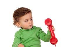 有使用与一个红色电话的一岁的婴孩 免版税库存图片