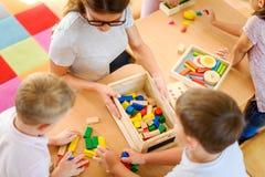 有使用与五颜六色的教诲玩具的孩子的学龄前老师在幼儿园 免版税库存照片