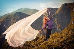 有使用与在山的风的浅粉红色的织品的女孩 免版税库存照片