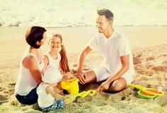有使用与在海滩的玩具的两个孩子的父母 免版税库存照片