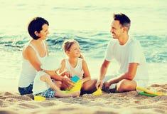 有使用与在海滩的玩具的两个孩子的父母 免版税图库摄影