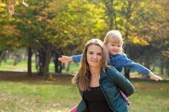 有使用与她的女儿的微笑的愉快的妈妈在公园在一个夏日 免版税库存图片