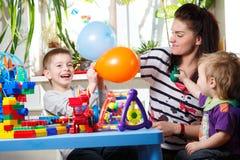有使用与气球的两个孩子的妇女 免版税库存图片