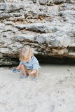 有使用与海滩沙子的玩具摩托车的孩子 免版税库存图片