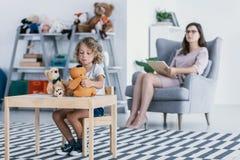 有使用与玩具的创伤的一个哀伤的孩子和坐在一把扶手椅子的一位专业心理学家在背景中 库存照片