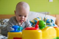 有使用与玩具的唐氏综合症的逗人喜爱的男婴 免版税库存照片