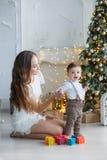 有使用与色的块的小儿子的妈妈在圣诞树附近 库存照片