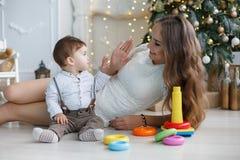 有使用与色的块的小儿子的妈妈在圣诞树附近 免版税图库摄影