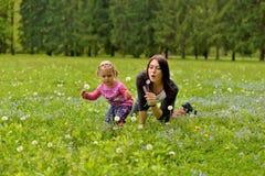 有使用在一个绿色草甸的一个小女儿的一个年轻母亲 免版税库存照片