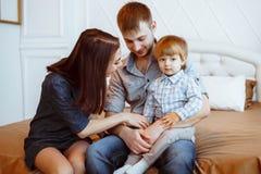 有使用在与玩具的床上的孩子的父母 免版税库存照片