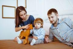 有使用在与玩具的床上的孩子的父母 库存照片
