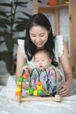 有使用在与smil的床上的男婴的愉快的亚裔家庭母亲 库存图片