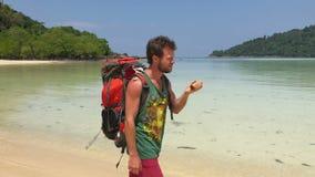 有使用在他的振动器的旅游背包的愉快的远足者人,当走由热带时温暖的水的天蓝色海岸线  股票录像