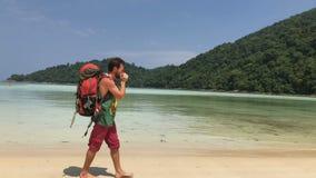 有使用在他的竖琴的旅游背包的愉快的远足者人,当走由热带时温暖的水的天蓝色海岸线  股票视频
