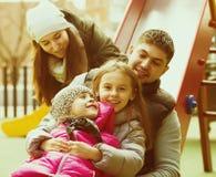 有使用在儿童` s的两个女儿的父母滑 免版税图库摄影