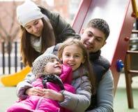 有使用在儿童` s的两个女儿的父母滑 免版税库存图片