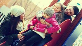 有使用在儿童` s的两个女儿的父母滑 免版税库存照片