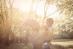 有使用在公园的女儿的非裔美国人的母亲 免版税库存照片