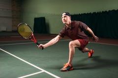 有使用在室内法院的网球拍的人 图库摄影
