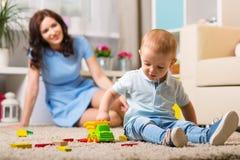 有使用在家的孩子的母亲 免版税图库摄影