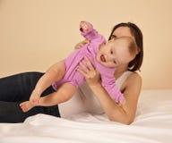 有使用在床上的婴孩的母亲 免版税图库摄影