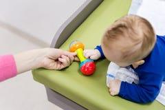 有使用在改变的桌上的母亲的婴儿 给吵闹声玩具的妈妈男婴 在视图之上 免版税库存照片