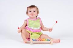 有使用在木琴的兴奋的女孩隔绝在白色 免版税库存照片