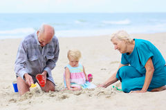 有使用在海滩的孙女的祖父母 库存图片