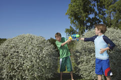 有使用在灌木中的水枪的男孩 免版税图库摄影