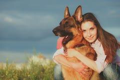 有使用在草坪的一只德国牧羊犬的年轻美丽的女孩 库存照片