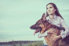 有使用在草坪的一只德国牧羊犬的年轻美丽的女孩 免版税库存照片