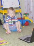 有使用在计算机和手机上的长的白肤金发的卷发的逗人喜爱的滑稽的矮小的男婴 库存图片