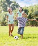 有使用在足球的父母的十几岁的男孩 免版税库存图片